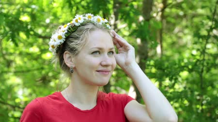 camomila : Beautiful woman with a wreath of daisies on a background of trees.
