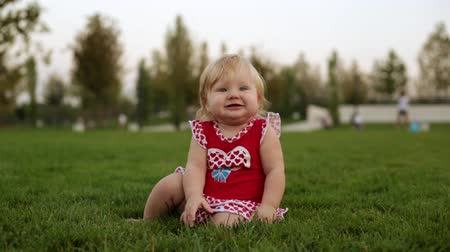 playful infant : A young child is sitting on the grass in the park.