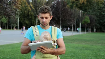 держит : A man with a child in a child carry or sling.