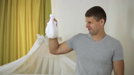 mal cheiroso : Man and childrens diaper. The man looks at the dirty diaper with disgust.