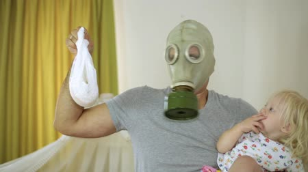 mal cheiroso : child and the man in a gas mask with disgust holding a diaper.