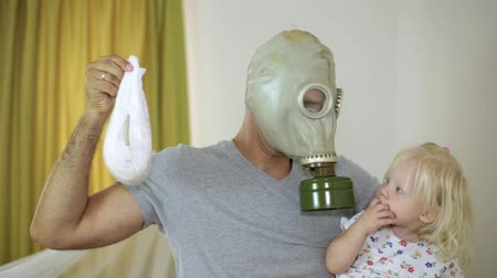 mal cheiroso : A man in a gas mask holding a baby and a diaper Stock Footage
