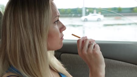 distraído : Woman is eating snack in the car. Vídeos