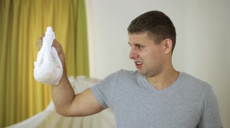 know : man with disgust is holding a dirty baby diaper.