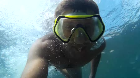 submerge : Crazy diver in a mask under the water.