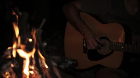 guitarrista : A man plays a guitar at night by the fire. Vídeos