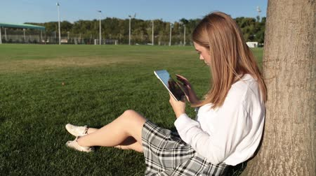 ebook : Young woman with a tablet in the park.