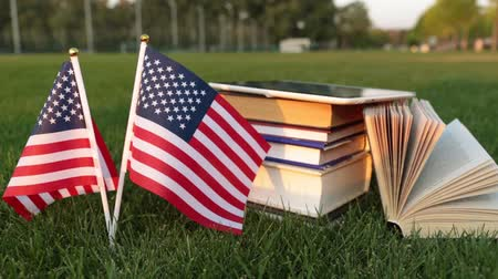 biblioteca : Books and the US flag on the grass. Study in America.