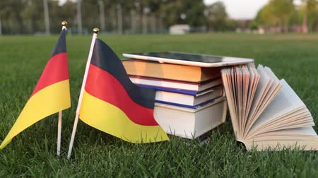 keménytáblás : German language and education. Flag of Germany and books on the grass.