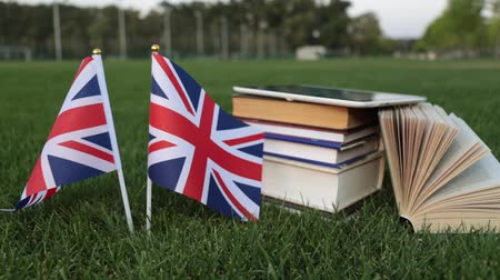 keménytáblás : Flag of Great Britain and books on the grass. Education in England, English.