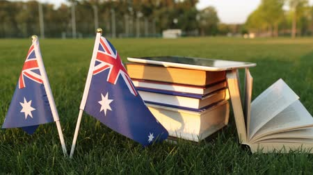 keménytáblás : Australian flag and books on the grass. Education in Australia.