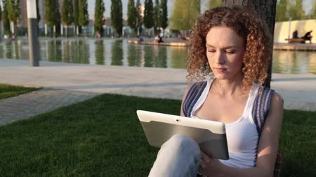 ped : Young modern woman with a tablet in the park.