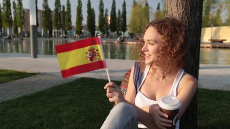 happiness symbol : Beautiful female tourist in the park with the flag of Spain.