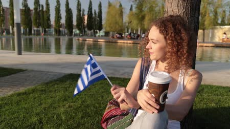 happiness symbol : Beautiful female tourist in the park with the flag of Greece.