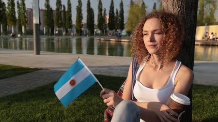 happiness symbol : Beautiful female tourist in the park with the flag of Argentina. Stock Footage