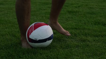 kop : A man is playing with a soccer ball on the grass. Footballball slow-motion. Dostupné videozáznamy