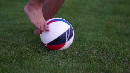 kop : Soccer ball and green grass. Man with a soccer ball, slow motion.
