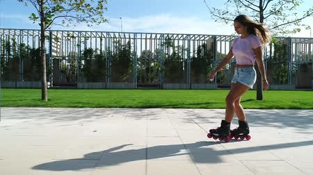 delgado : Young sporty woman rollerblading, slow motion. Girl on the rollers in the park. Vídeos