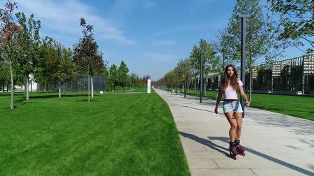 delgado : Young beautiful woman riding on roller skates in the park.