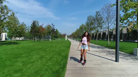 rolki : Girl on the rollers in the park. Young sporty woman rollerblading, slow motion.