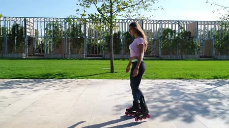rolki : Young girl on the rollers. Beautiful woman in the park on roller skates. Wideo