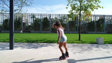 delgado : Beautiful woman in the park on roller skates. Young girl on the rollers.