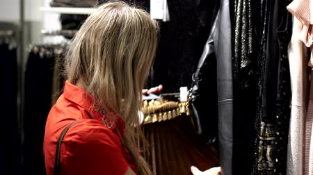 vállfa : Young woman in a clothing store. Stock mozgókép
