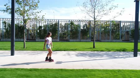 rolki : Beautiful young woman is rollerblading in the park. Girl on the rollers.