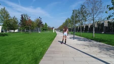 giostre : Beautiful woman rollerblading in the park. Girl rides on roller skates.