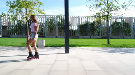 paten yapma : Sexy woman rollerblading in the park. Sports girl rides on roller skates. Stok Video