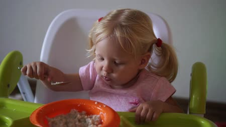 vork : The child eats at the table, slow motion. Stockvideo