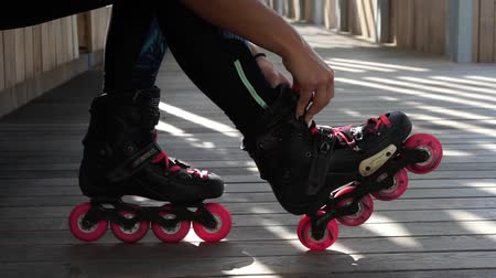 inline skating : Woman shoes roller skates, close-up.