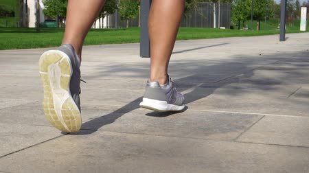 warming up : A woman runs in the park. Womens sneakers, close-up. Stock Footage