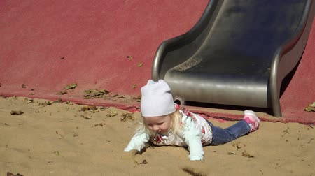 plac zabaw : The child rolls down a hill. The girl rides a slide in the playground.