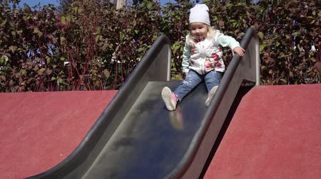 plac zabaw : A girl slides down a slide in a childrens playground. The child rolls down a hill.