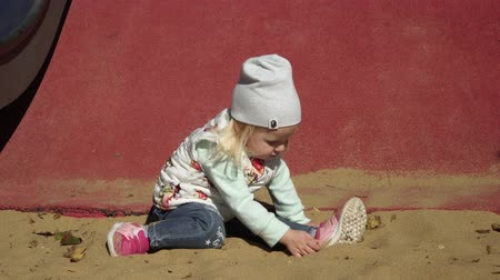 plac zabaw : A child plays in the sandbox on the playground. Wideo