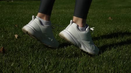 geri yaktı : Woman doing fitness on green grass. Female sneakers.