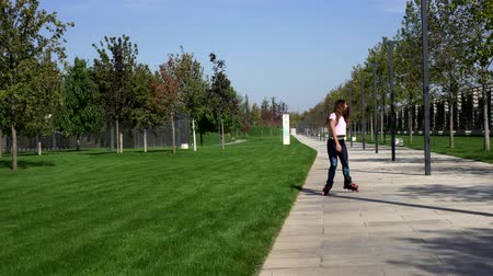 roller blading : Beautiful young woman roller skating in the park. Stock Footage