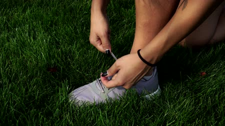 cipőfűző : Woman shoes sneaker on the background of grass.