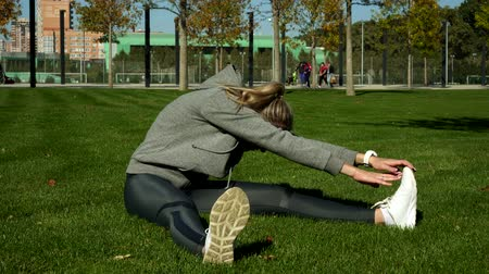 listening music : Young woman goes in for sports in the park. Stock Footage
