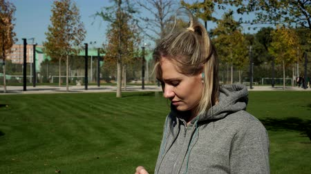 이어폰 : Woman athlete listening to music in the park using a smartphone. 무비클립