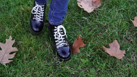 wrzesień : Autumn, a woman walks through the foliage. Womens shoes close-up.