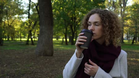 elvihető : Autumn, a young woman drinks coffee in the park. Slow motion.