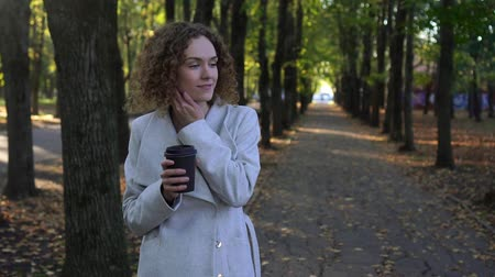 навынос : Beautiful young woman with curly hair is drinking coffee in the autumn park. Стоковые видеозаписи