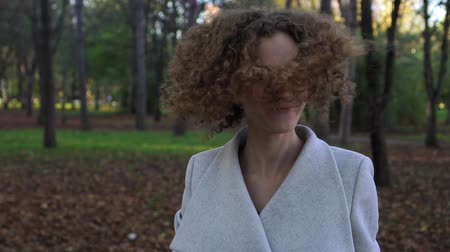 кудри : Portrait of a young beautiful woman with curly hair in autumn park. Стоковые видеозаписи