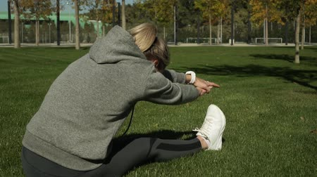 listening music : A young woman doing fitness in the park.
