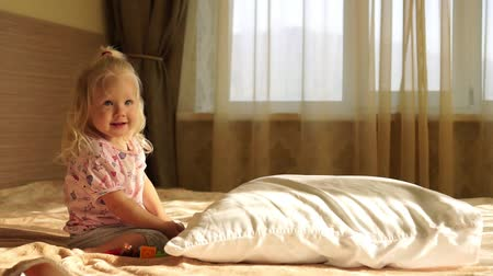almofadas : Little baby girl on the bed playing with toys, slow motion. Stock Footage