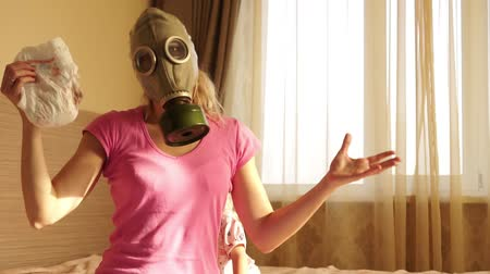 unpleasant smell : A woman in a gas mask with a dirty diaper.