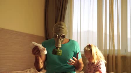 unpleasant smell : A young father in a gas mask holding a dirty babys diaper.