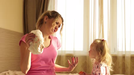 unpleasant smell : The woman with disgust holding a dirty baby diaper. Motherhood, humor.